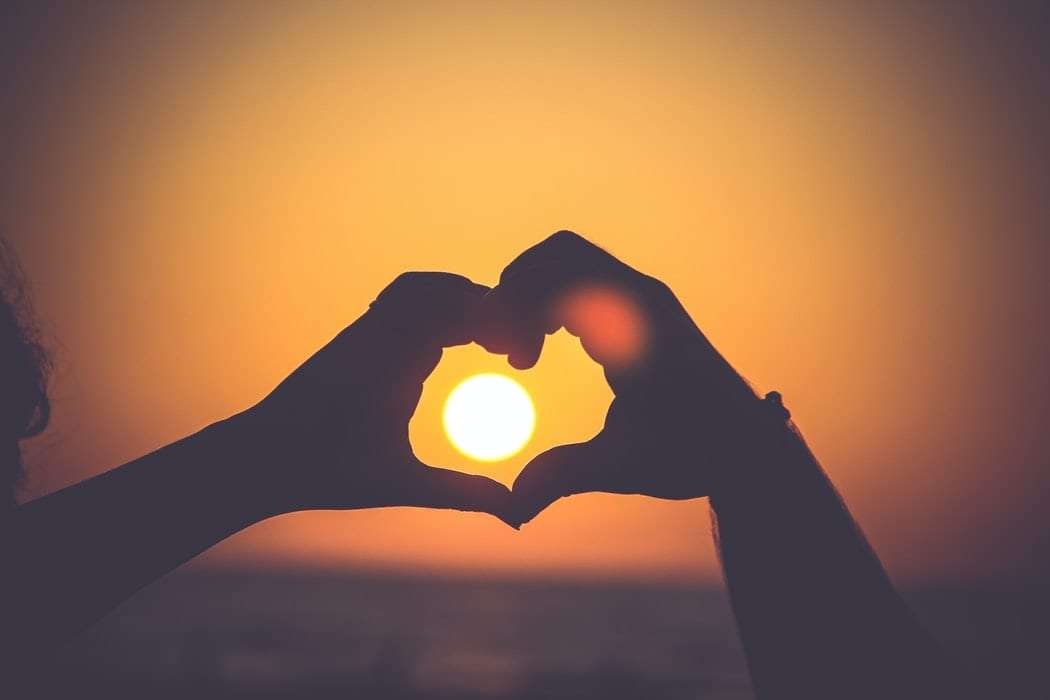 person's hands in shape of heart in front of sunset