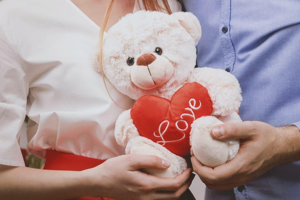 Couple holding plush toy bear