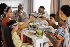 family clinking wine glasses during meal