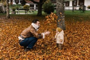 man and child playing in leaves